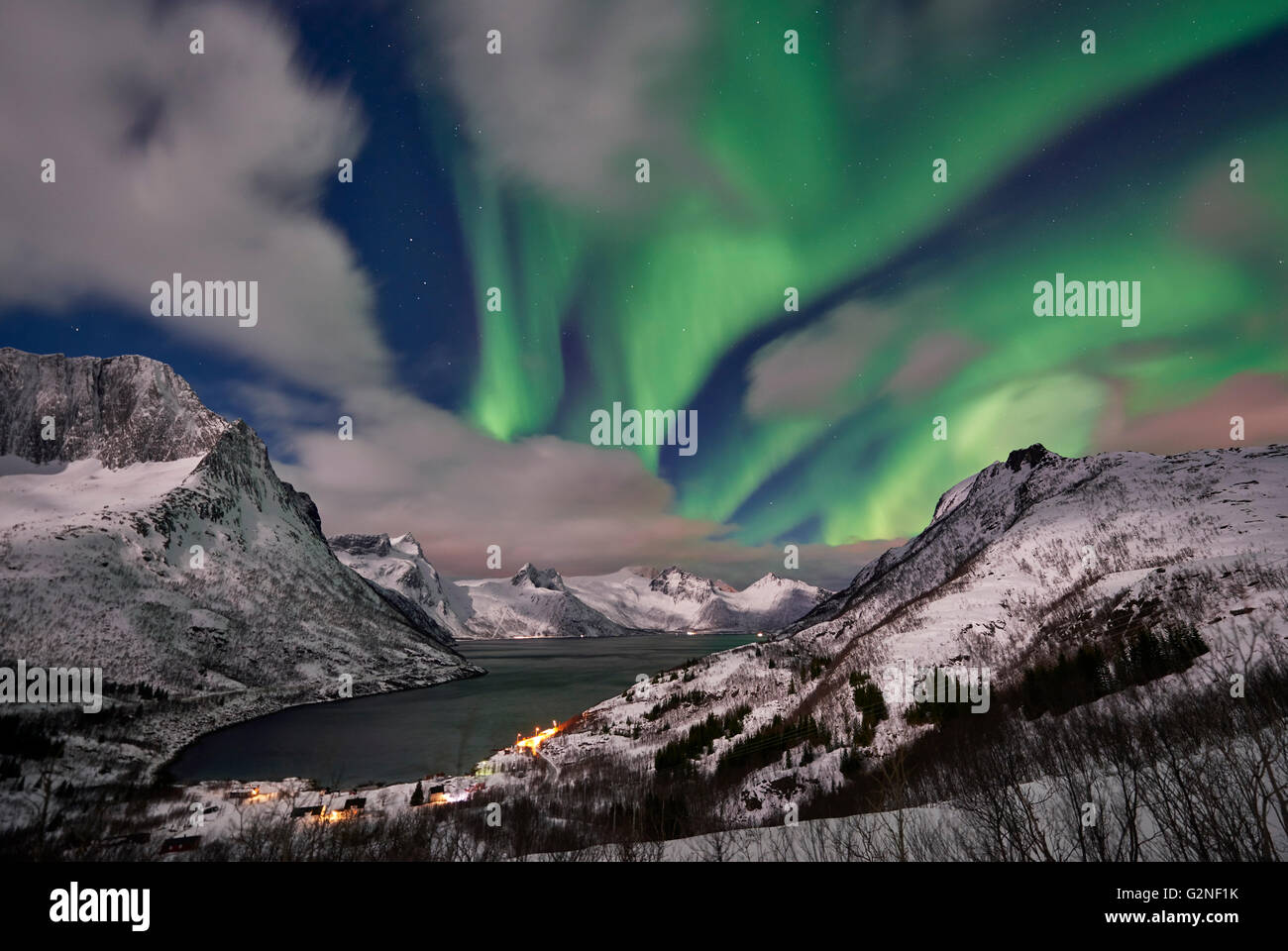 Aurora Borealis or northern lights over winter landscape in fjord of Mefjorden, Senja, Troms, Norway, Europe - Stock Image