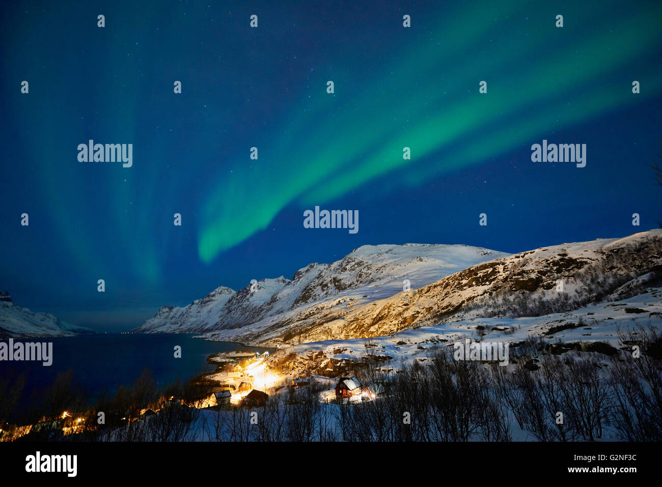 Aurora Borealis or northern lights over winter landscape in fjord of Ersfjordbotn, Tromsö, Troms, Norway, Europe - Stock Image