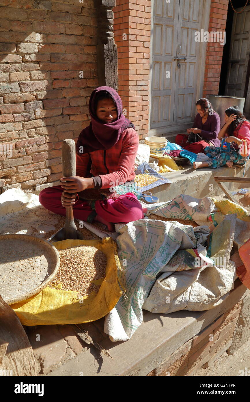 Young woman pounding the grain outside her home in the streets of Bhaktapur, Nepal - Stock Image