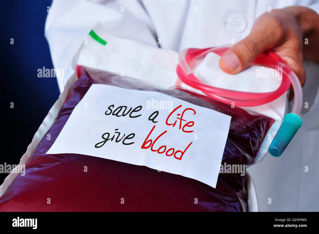 closeup of a young doctor man holding a blood bag with a white label with the text safe a life give blood written - Stock Image