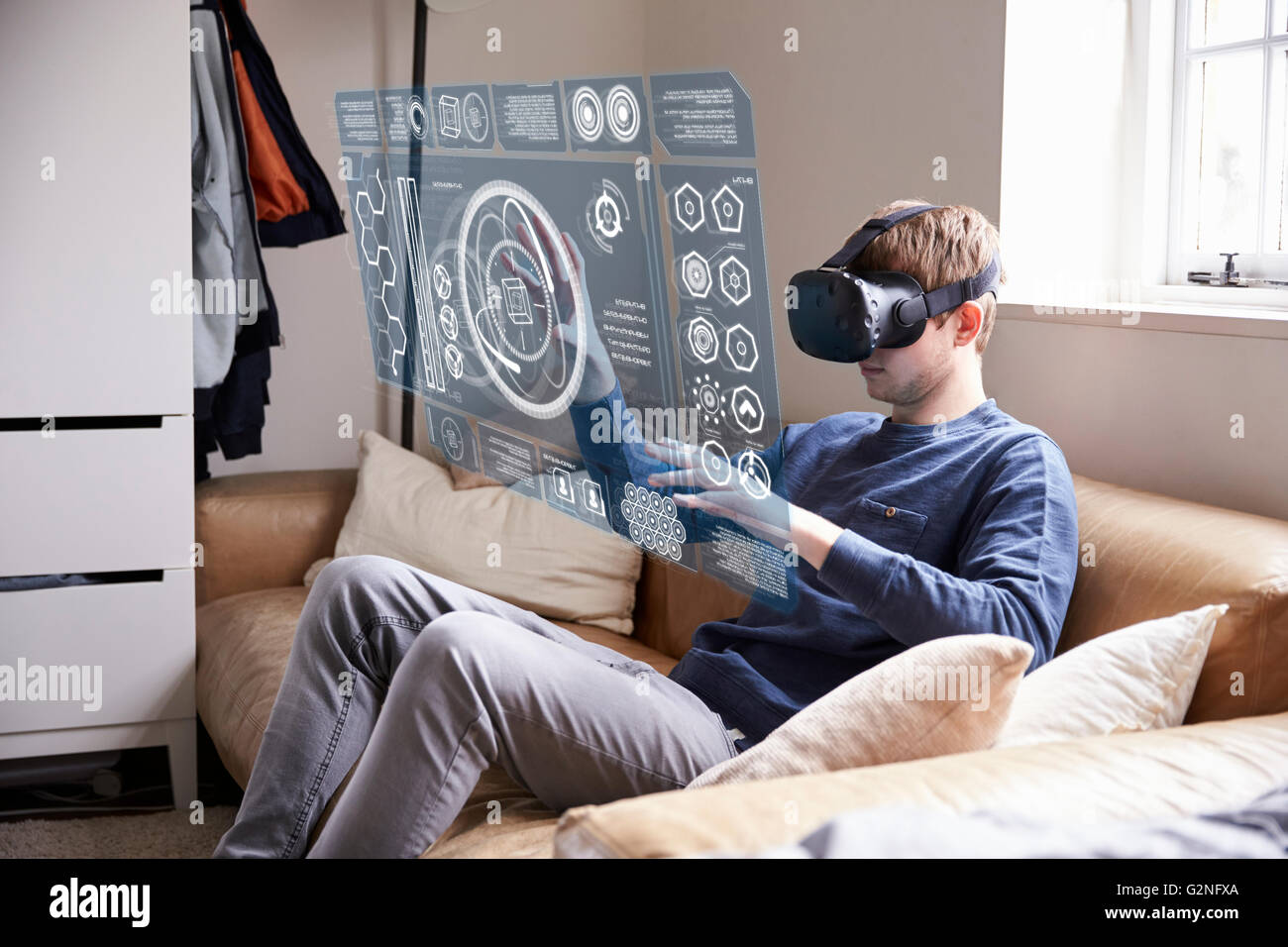 c1ece0e387d Man Sitting On Sofa At Home Wearing Virtual Reality Headset - Stock Image