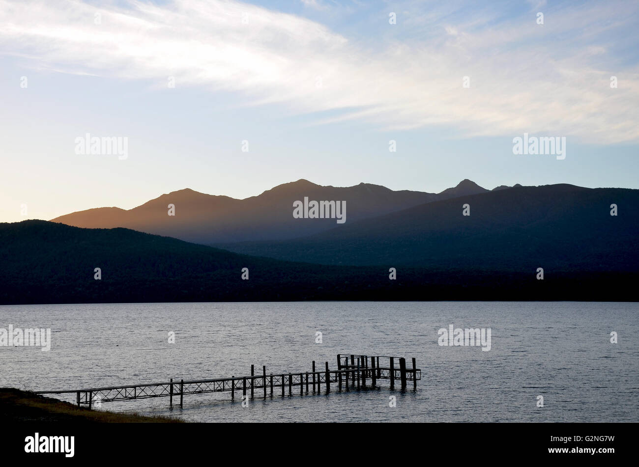 Dusk and wispy clouds over Te Anau lake, jetty and mountains in the pristine wilderness of fiordland, New Zealand - Stock Image