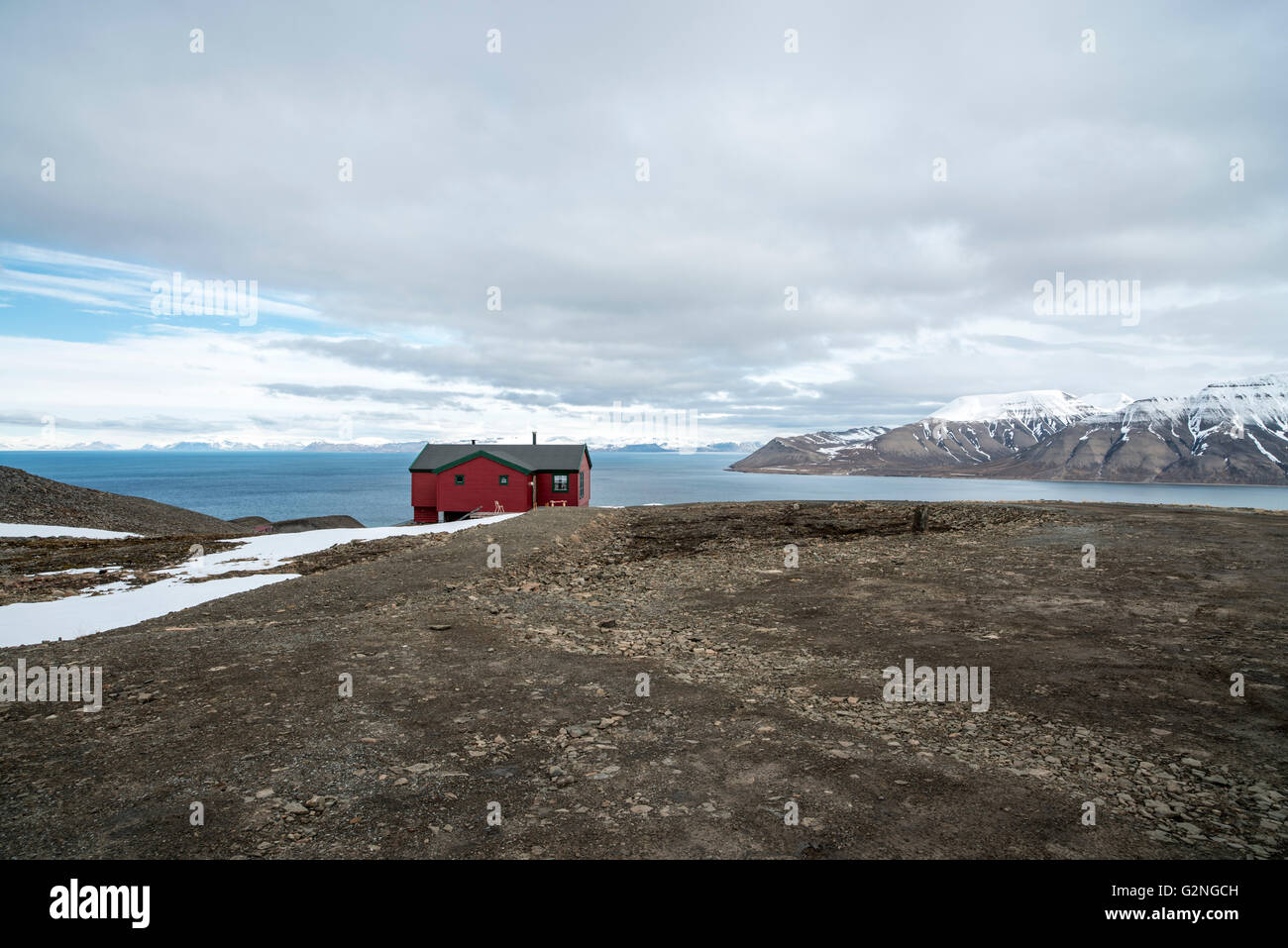 View over Adventfjorden, Svalbard, with red hut Spitsbergen Norway Rotes Holzhaus in der Bucht des Adventfjorden - Stock Image