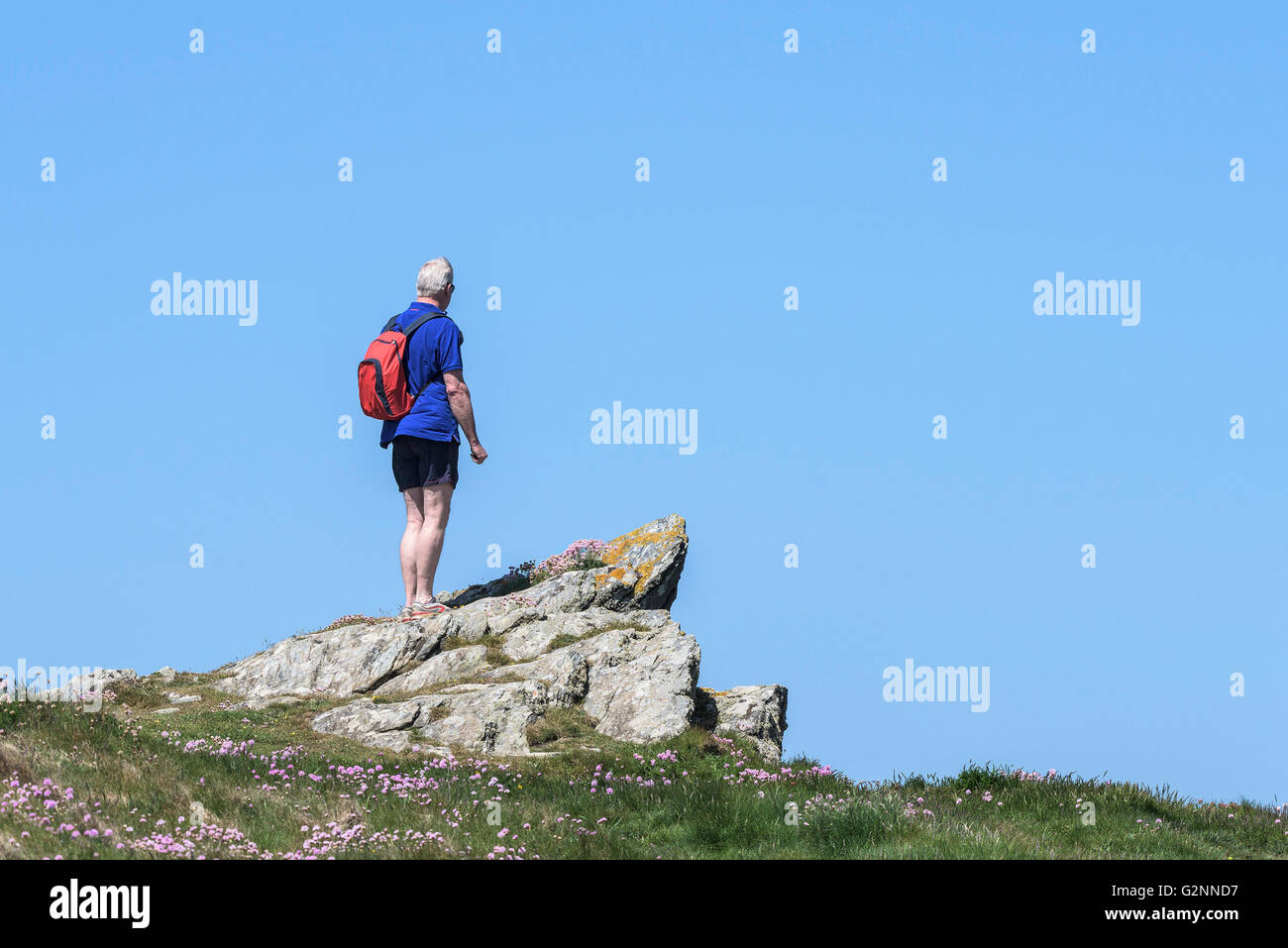 Sunny weather as a holidaymaker stands on East Pentire Headland in Newquay, Cornwall. - Stock Image