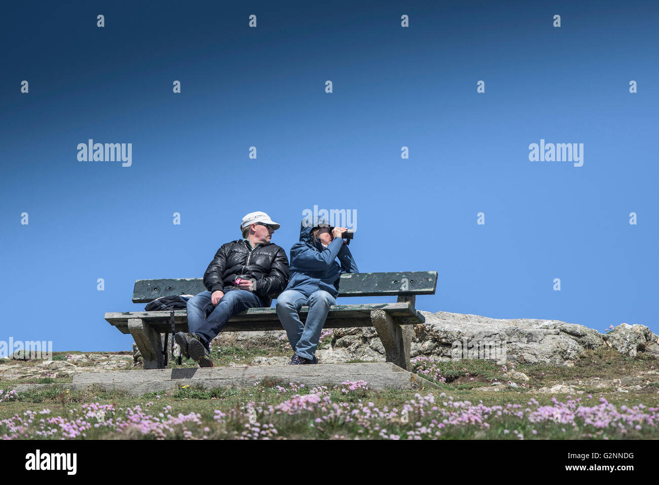 Sunny but windy weather as tourists sit on a bench on East Pentire Headland in Newquay, Cornwall. - Stock Image