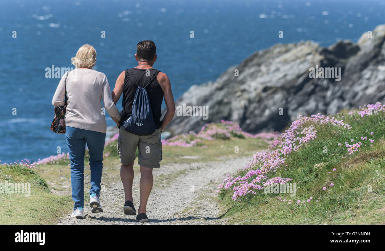 Sunny weather as holidaymakers enjoy a walk on East Pentire Headland in Newquay, Cornwall. - Stock Image