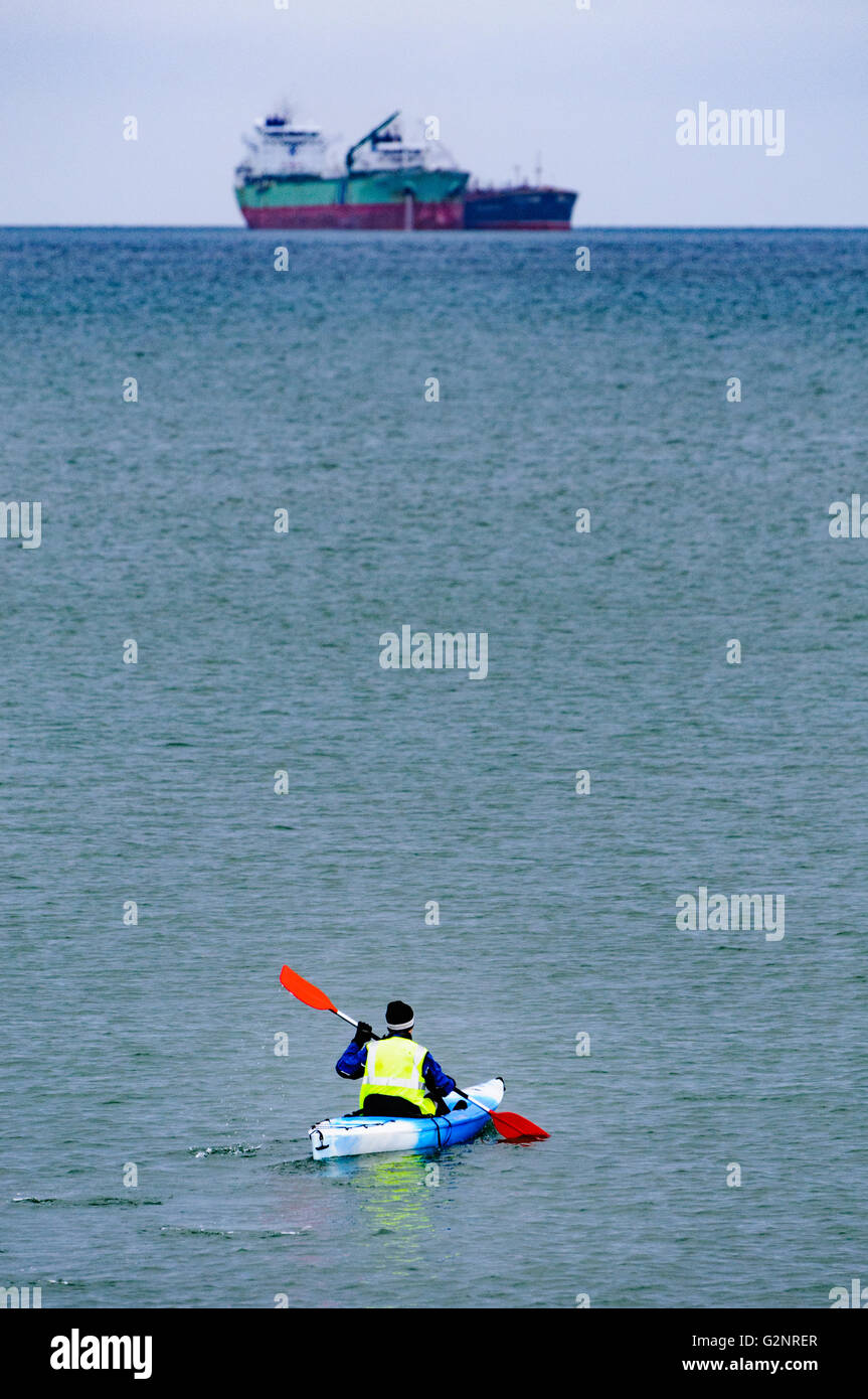 Belfast, Northern Ireland. 07/01/2012: A man in a kayak canoe paddles towards two oil tankers anchored far out at - Stock Image