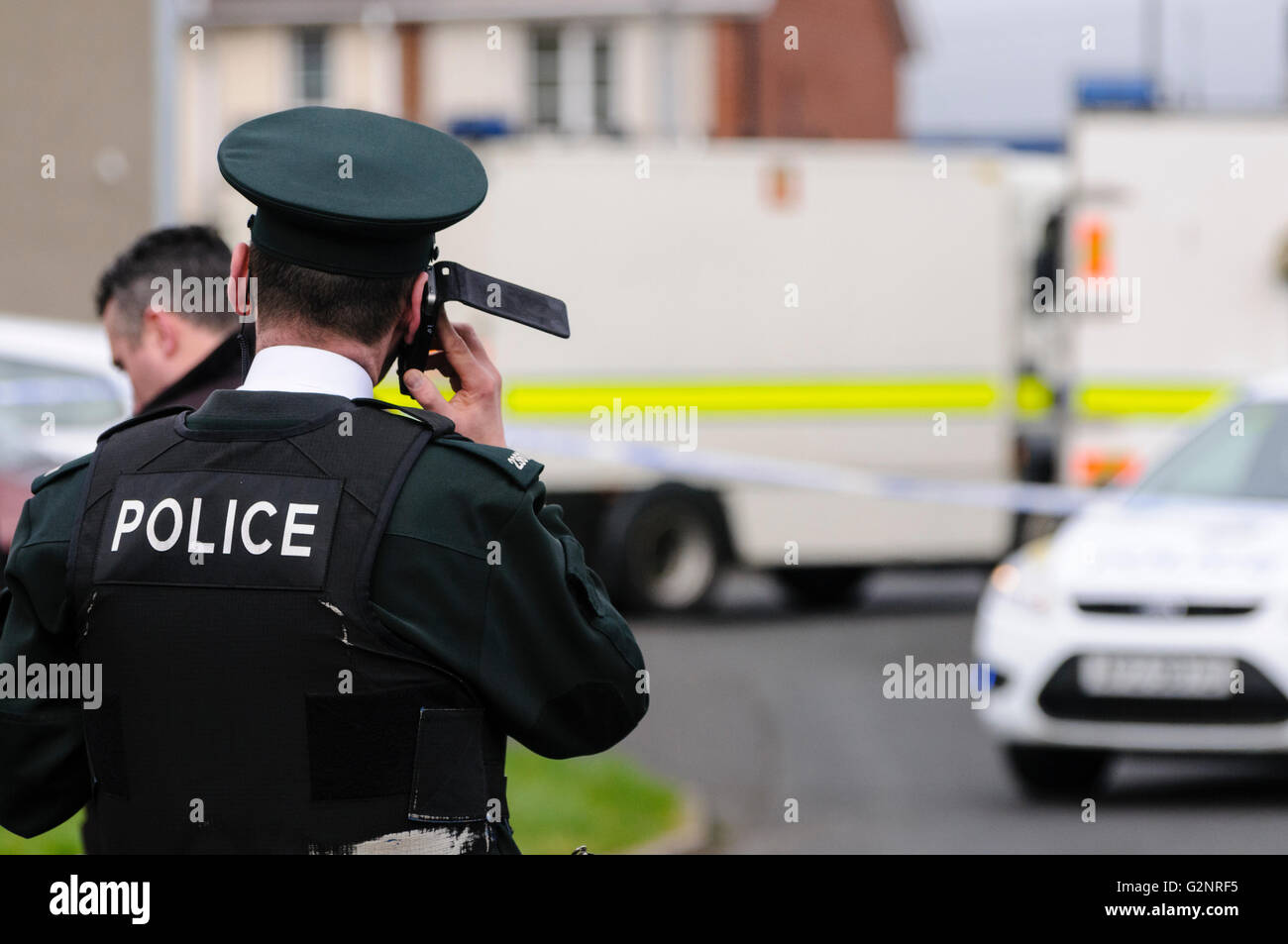 A PSNI police officer makes a telephone call during a bomb scare security alert in Rathcoole, NORTHERN IRELAND, - Stock Image