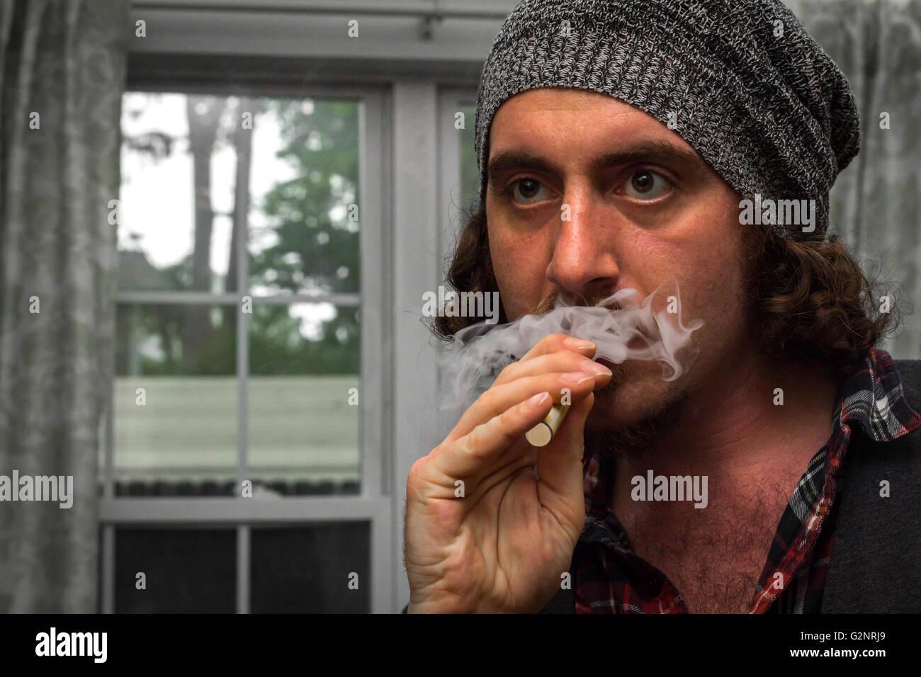 Long haired bearded man smokes a vape e-cigarette - Stock Image