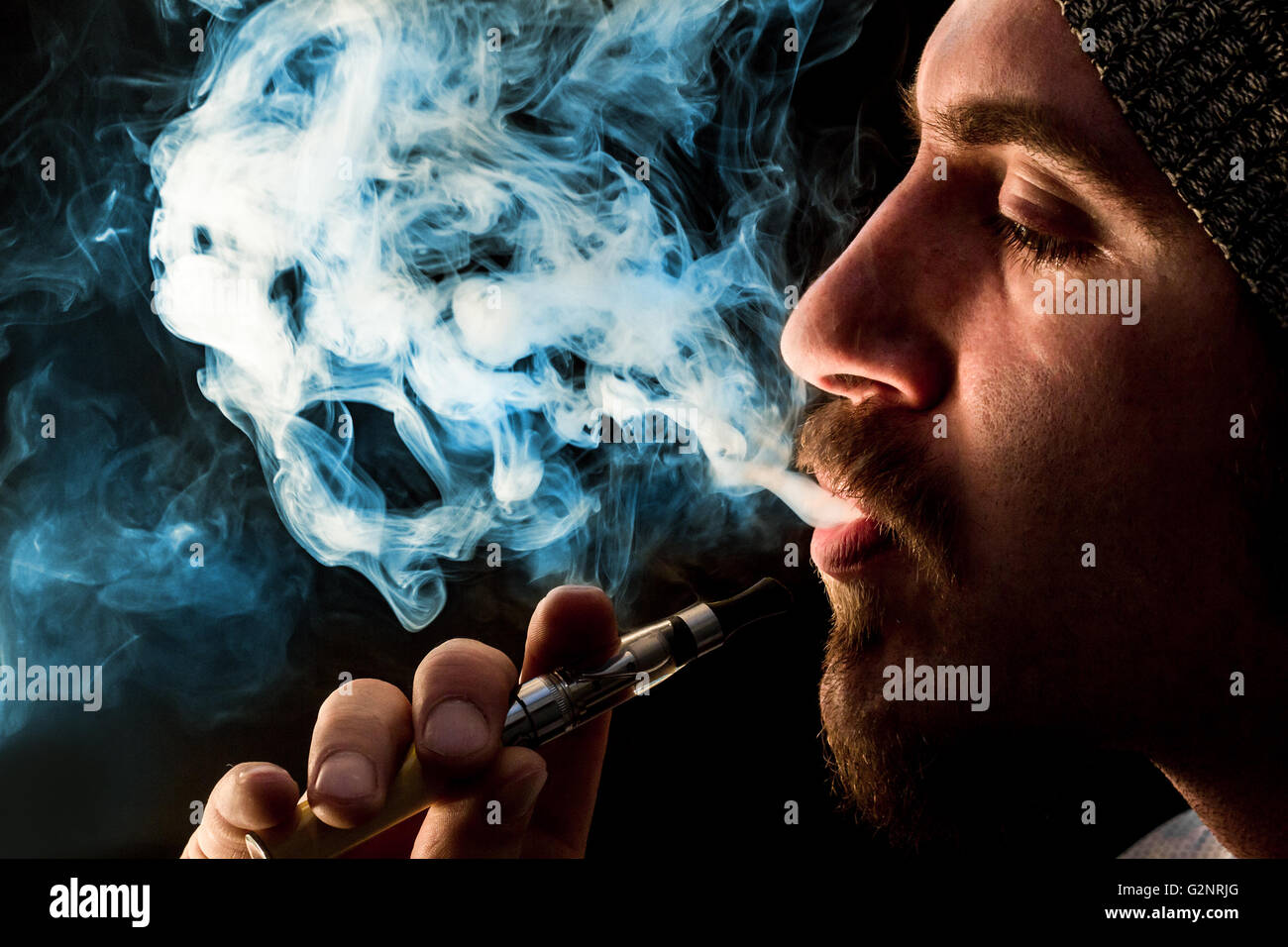 Dramatic lighting bearded man smokes a vape e-cigarette - Stock Image