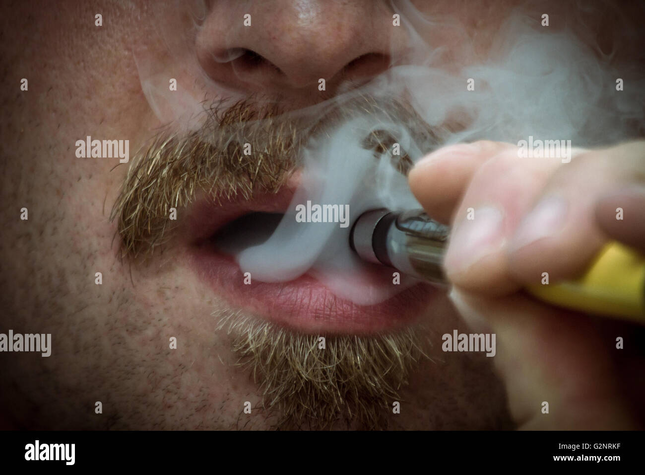 Bearded man smokes a vape e-cigarette in extreme closeup macro - Stock Image