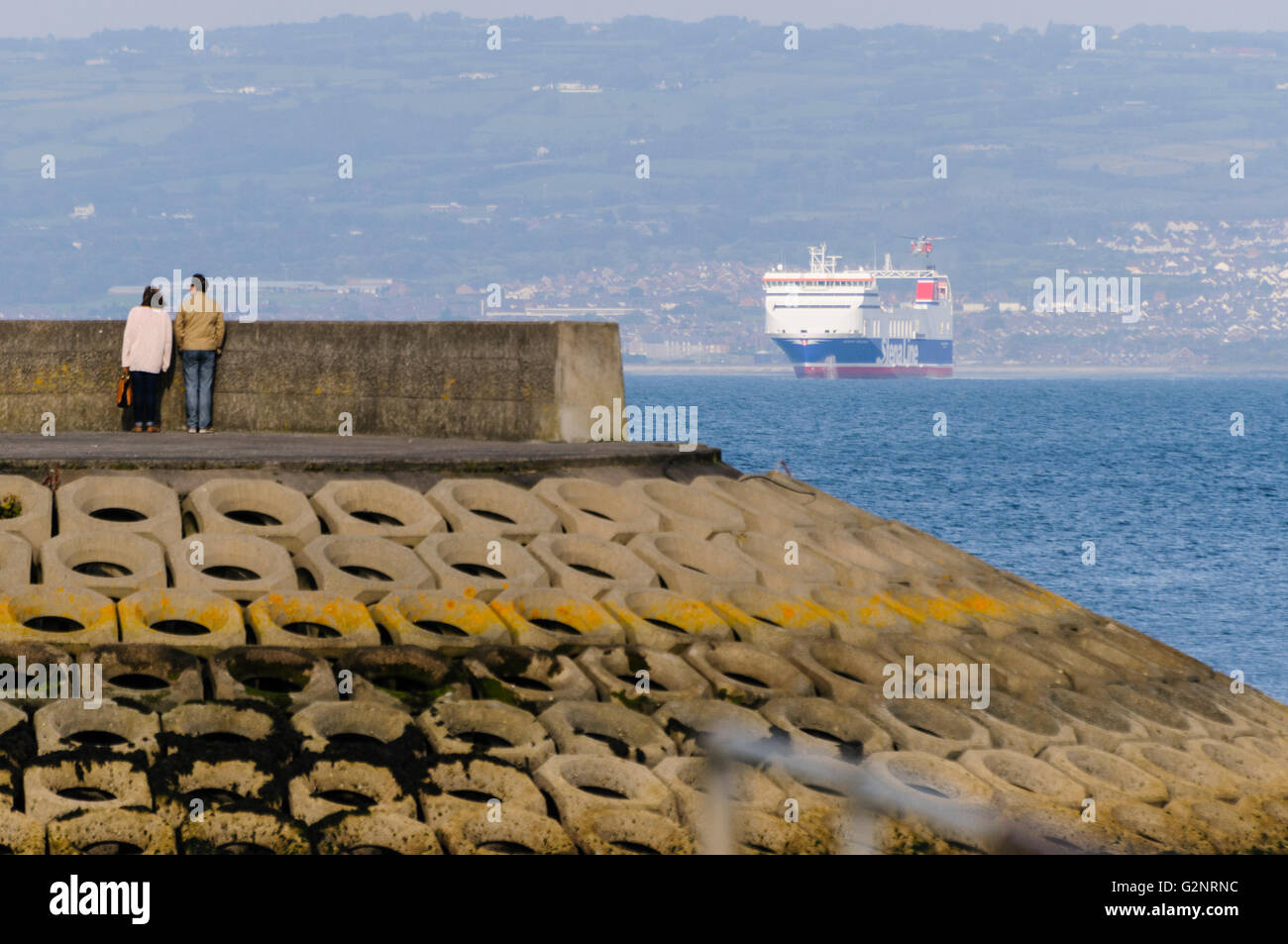 Bangor, County Down. 23/09/2012 - Two members of the public stand at the end of a pier, watching a large Stena Line Stock Photo