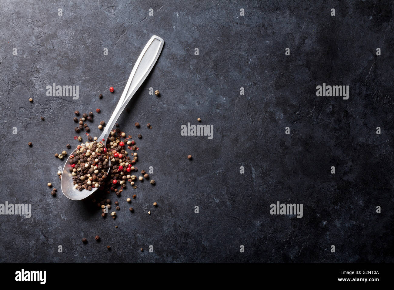Mixed peppercorn. Red, white and black pepper spices in spoon on stone table. Top view with copy space - Stock Image