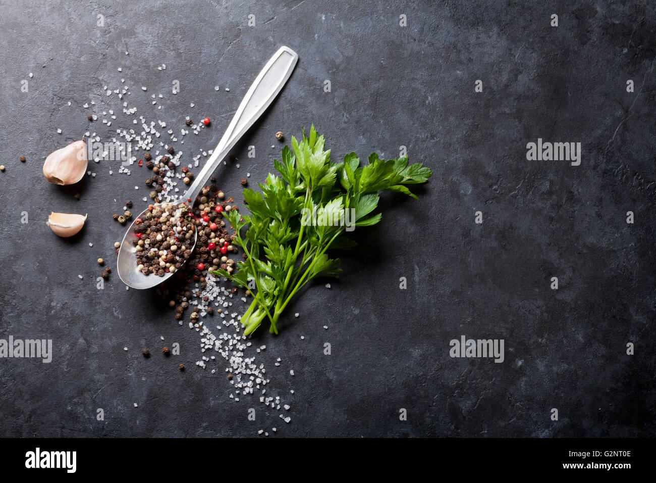 Garlic, black, white and red pepper and salt spices in spoon, parsley herb. Top view with copy space - Stock Image