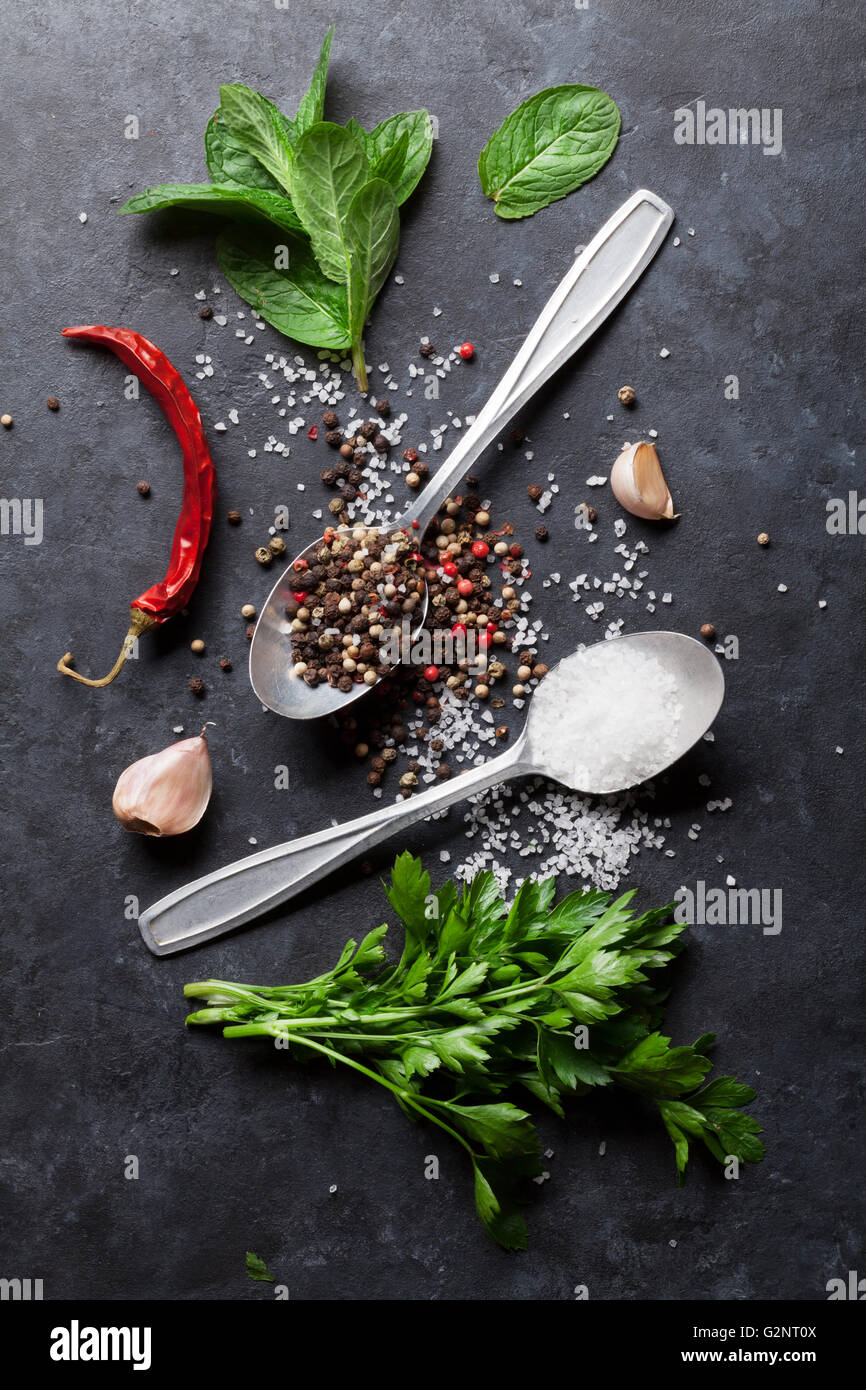 Black, white and red pepper and salt spices in spoon. Mint and parsley herbs. Top view - Stock Image