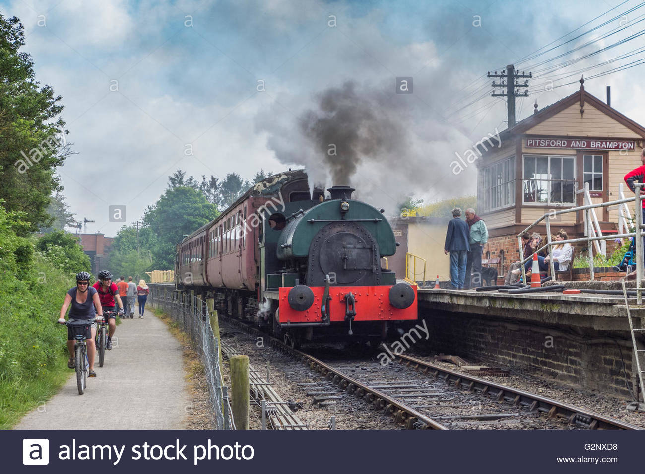 A train in the Pitsford and Brampton station on the Northampton and Lamport preserved steam railway as cyclist pass - Stock Image