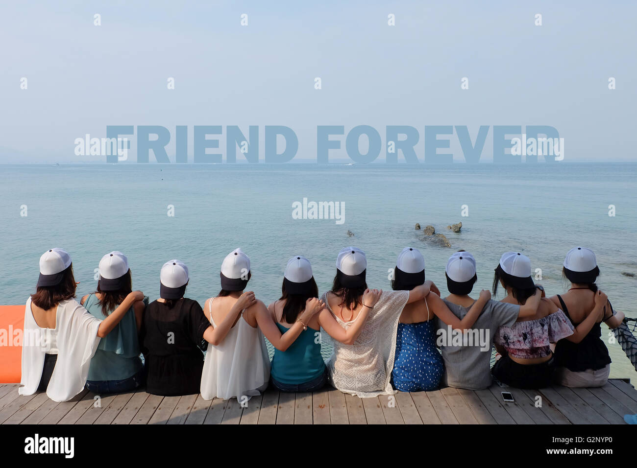group of ten women friends sit hug together look FRIEND  FOREVER blue sea sky - Stock Image