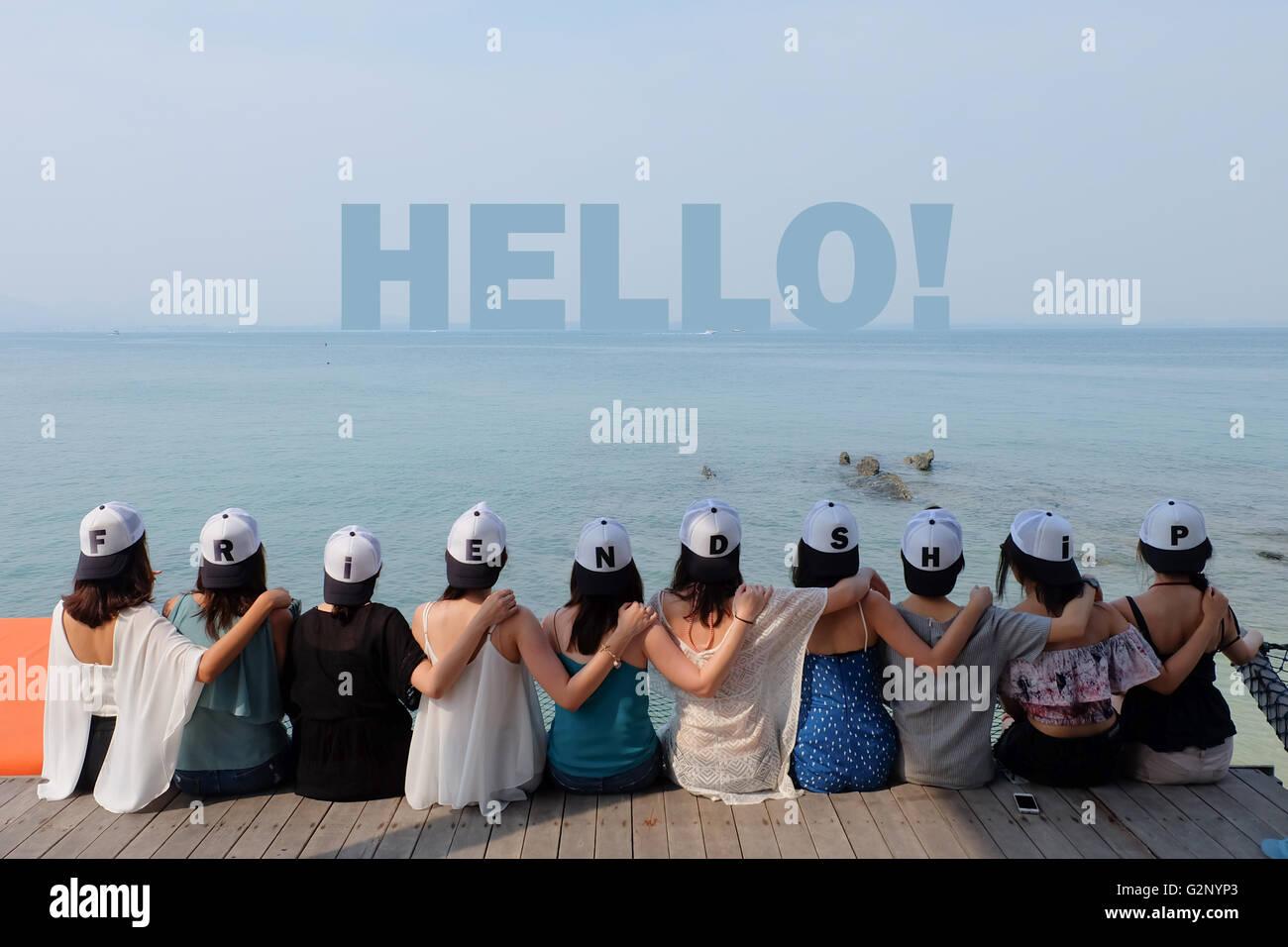 group of ten women friends sit hug together look HELLO! blue sea sky - Stock Image