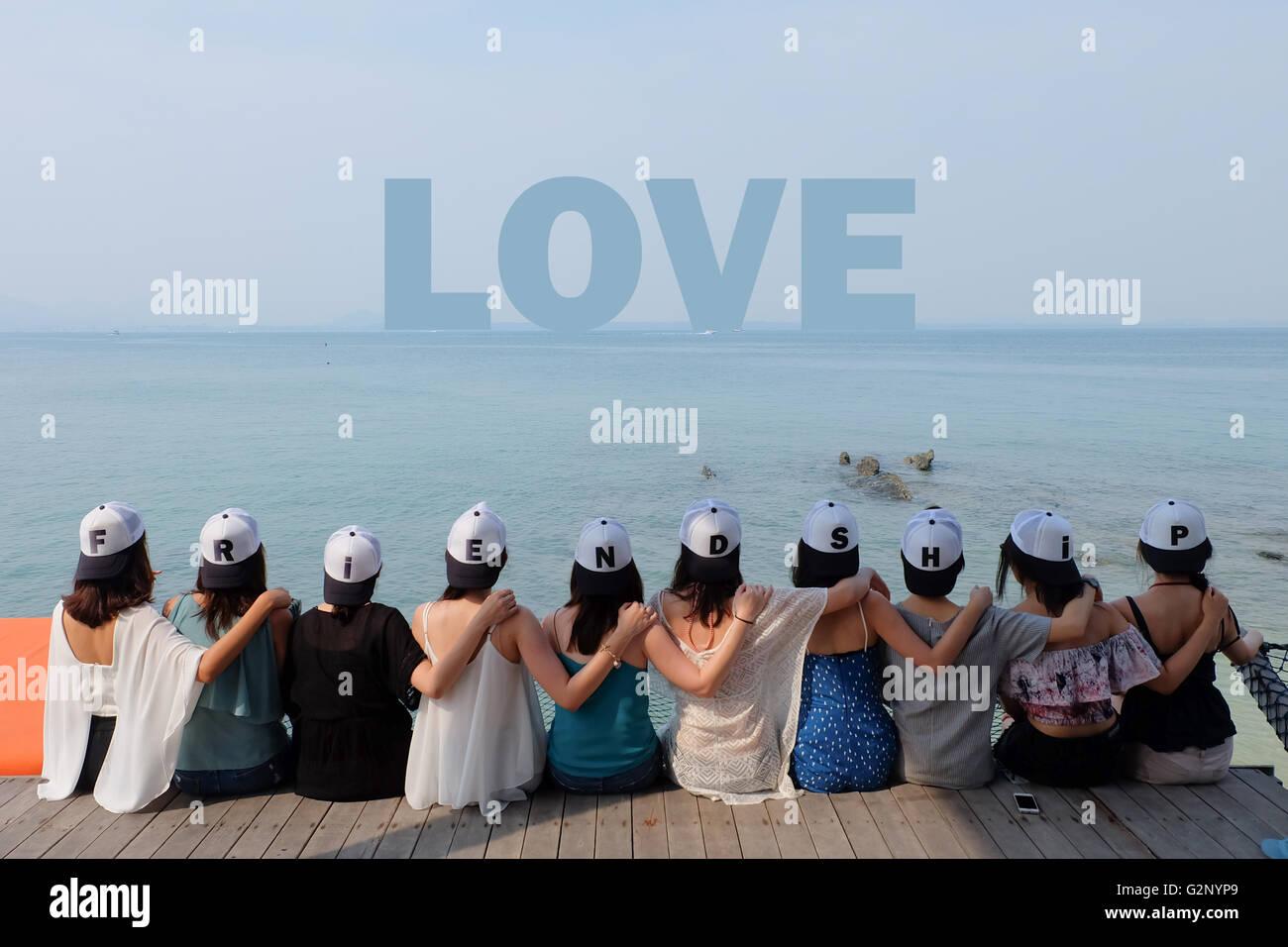 group of ten women friends sit hug together look LOVE blue sea sky. - Stock Image