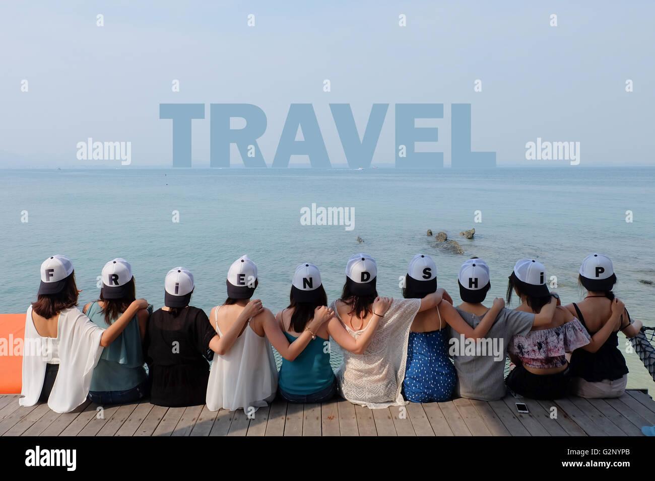 group of ten women friends sit hug together look TRAVEL blue sea sky. - Stock Image