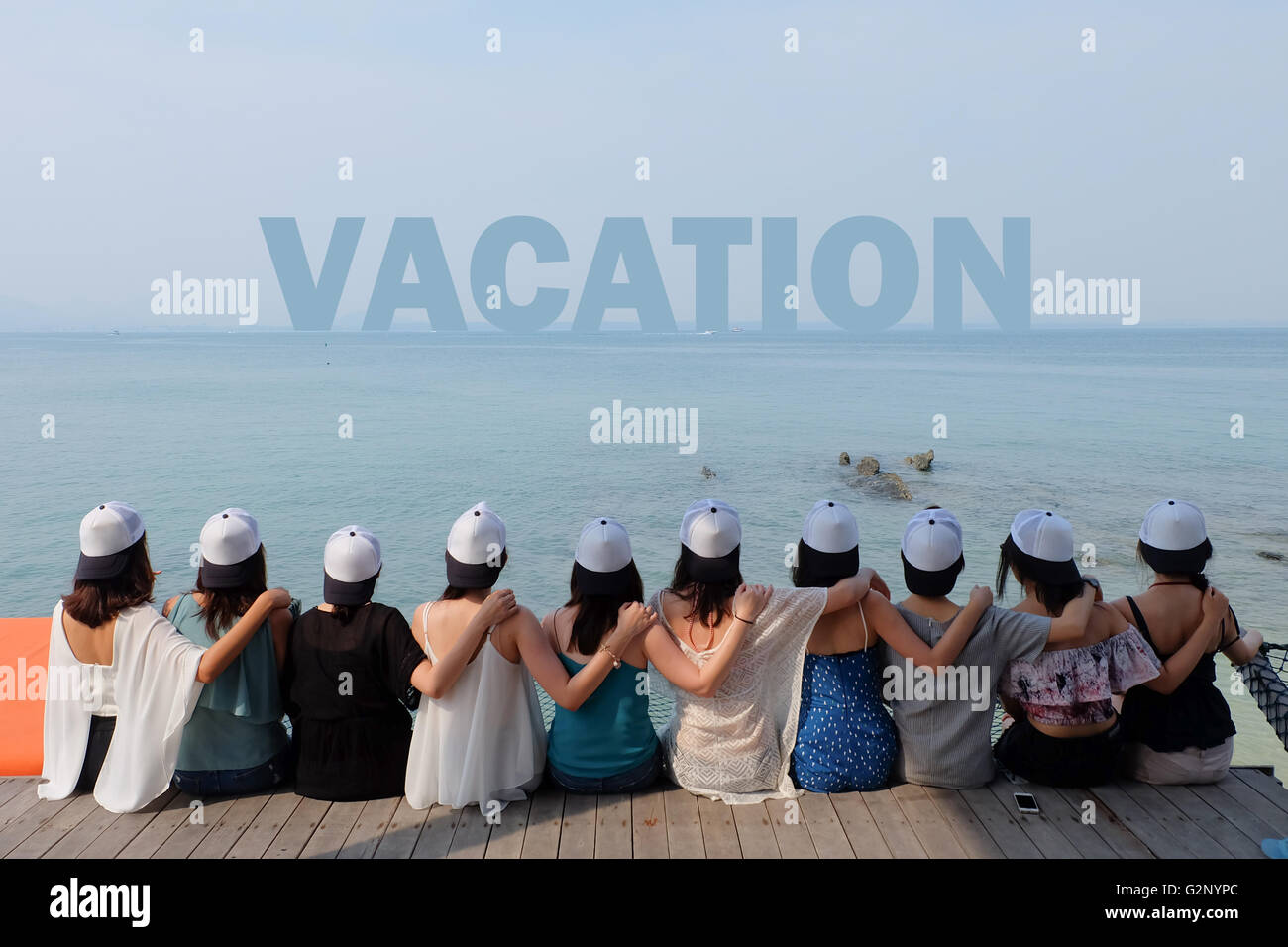 group of ten women friends sit hug together look VACATION blue sea sky. - Stock Image