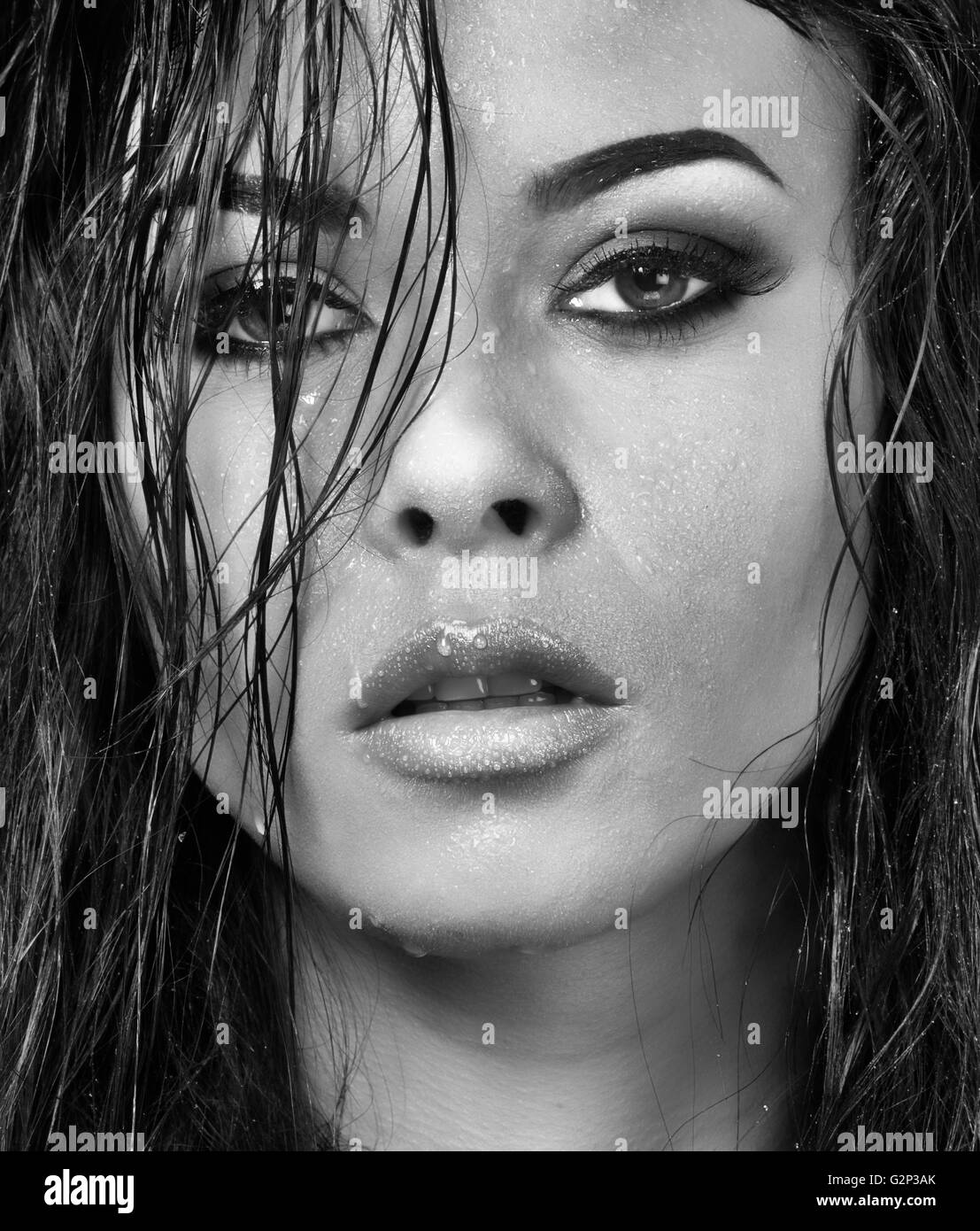 Black and white wet  faced beautiful model, with long hair and water droplets on sultry face - Stock Image