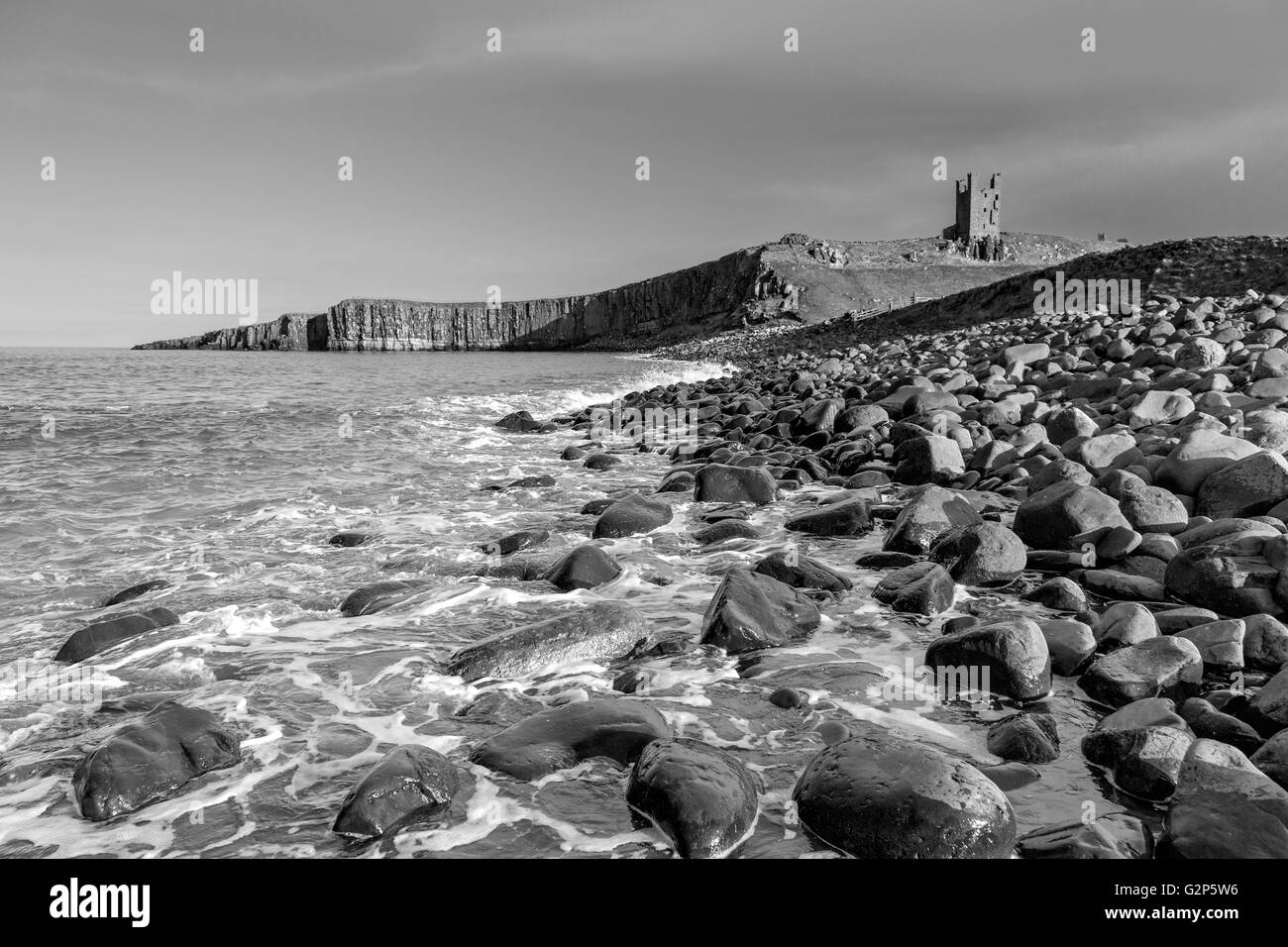 Dunstanburgh Castle in monochrome, on the north east coast of Northumberland, England, UK - Stock Image