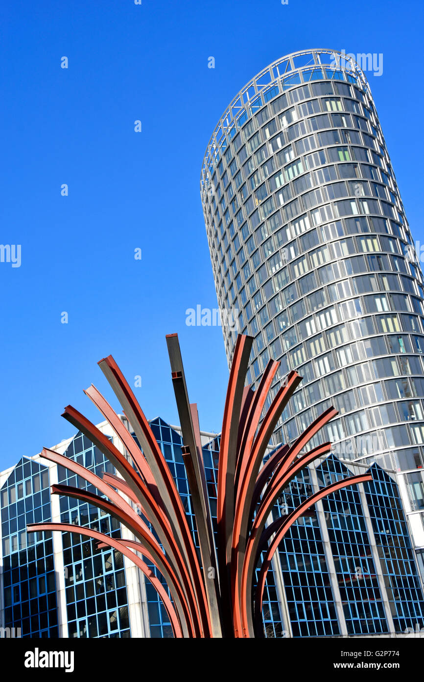 Part of curved steelwork sculpture Railway Tree by Malcolm Robertson and modern high rise Stratford office development - Stock Image