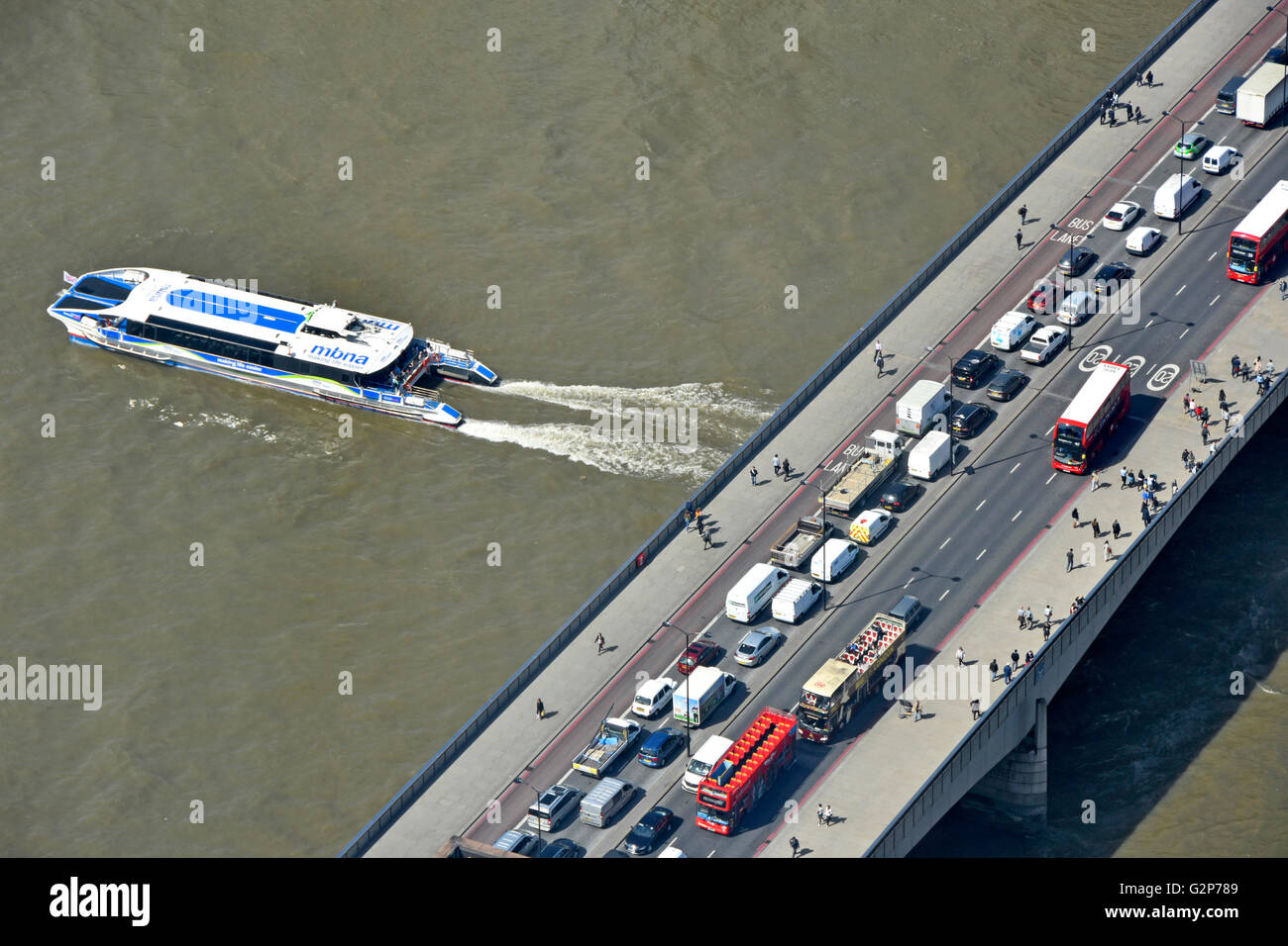 Aerial view from above of traffic jam and pedestrians on The London Bridge with Thames Clipper river bus service - Stock Image