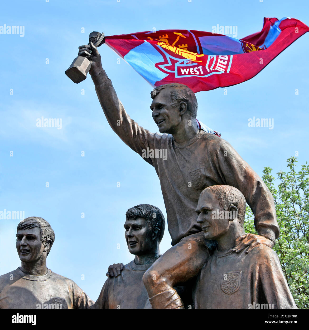 Part of World Cup football players sculpture statue featuring Bobby Moore with World Cup trophy and fans West Ham - Stock Image