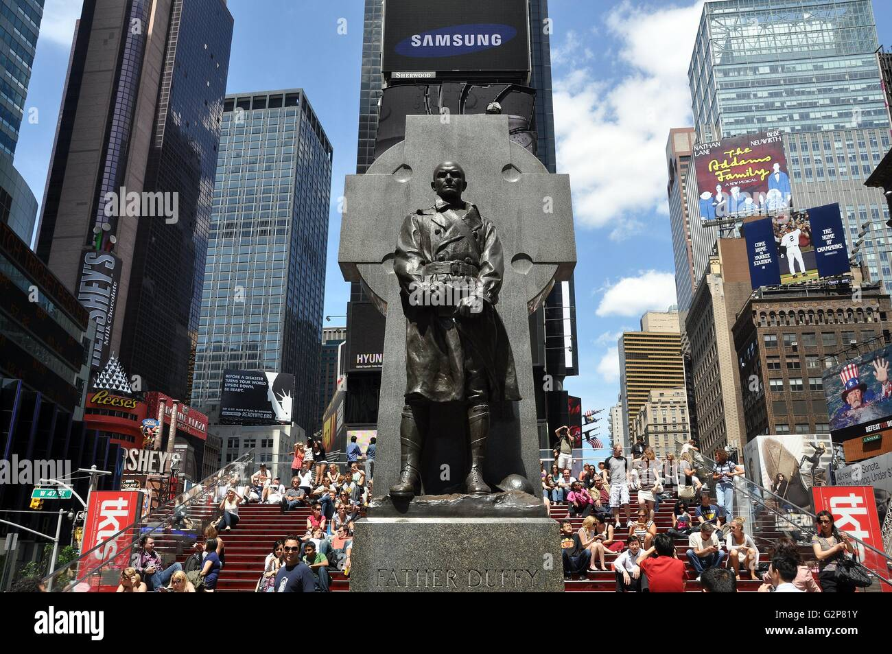 New York City:  Statue of Father Duffy stands at 46th Street in Duffy Square just south of the new TKTS booth - Stock Image