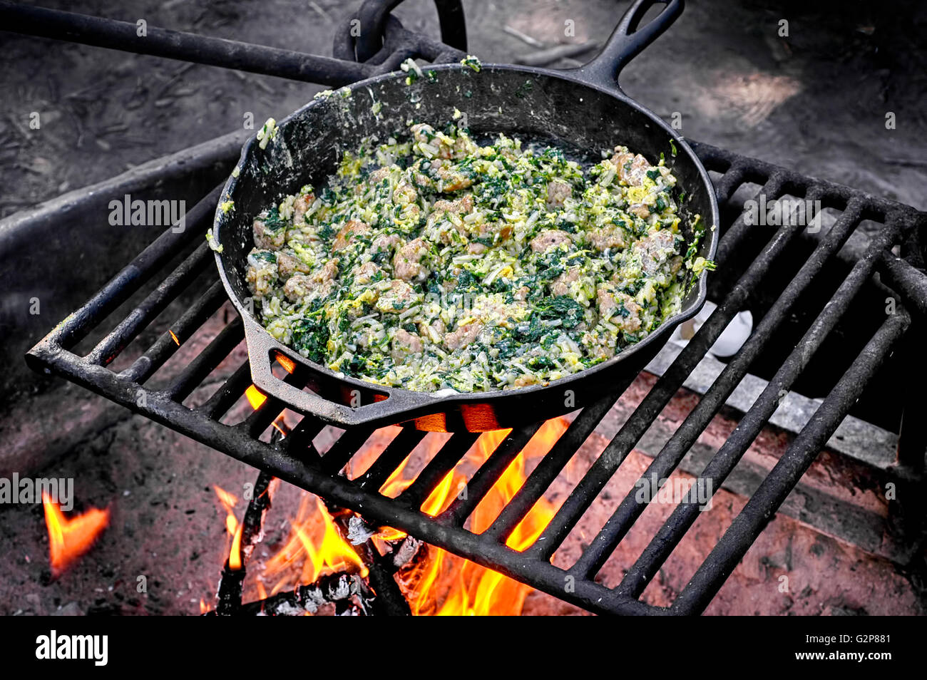 Sausage and spinach egg scramble cooked on a campfire in cast iron skillet - Stock Image