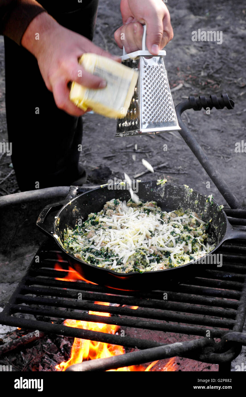 Sausage spinach and egg scramble cooked over a campfire grill - Stock Image
