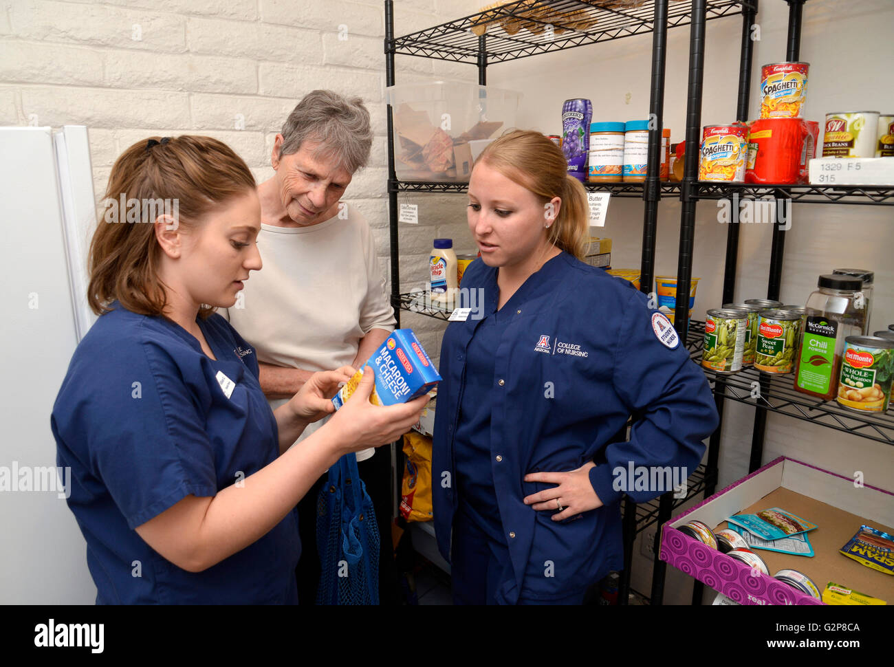Nursing students review food labels with a Miracle Square resident as part of their college training. - Stock Image