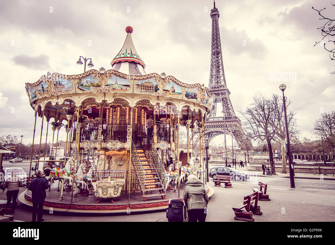 Paris, France - March 18, 2012: Children accompanied by their parents and grandparents play the carousel of the - Stock Image
