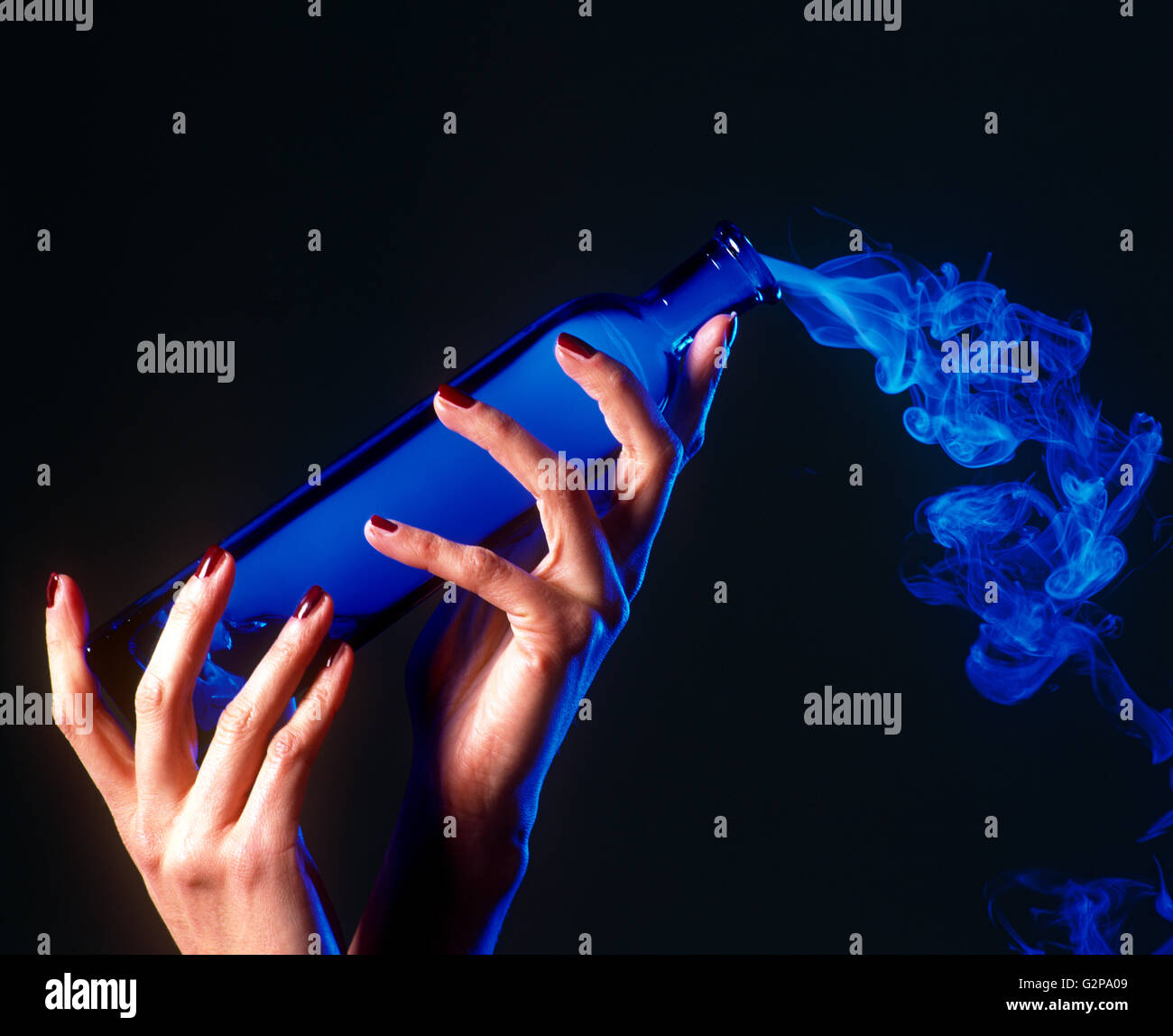A girls hands holding a bottle of blue smoke, indoors. - Stock Image