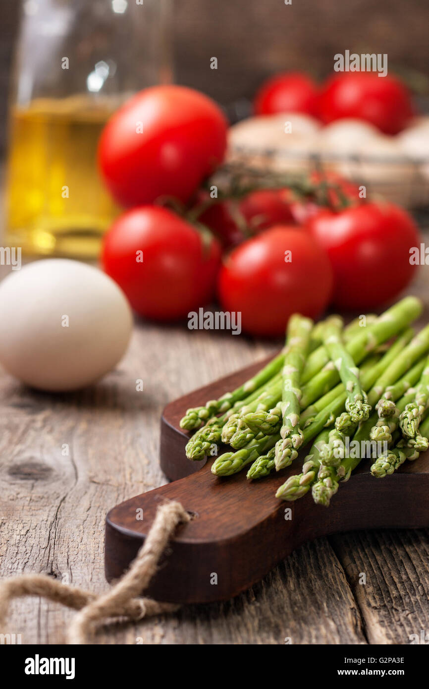 ingredients for cooking healthy dietary breakfast: fresh asparagus, tomatoes, eggs and olive oil on a wooden background - Stock Image