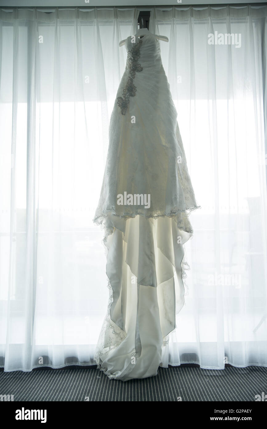 A traditional white wedding dress hung amongst four greyish blue bridesmaids gowns - Stock Image