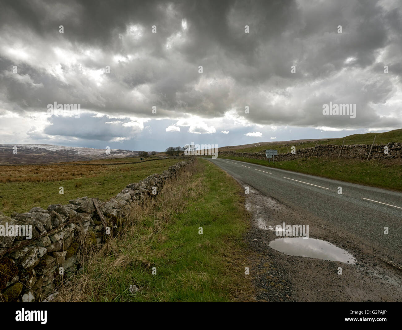 North Pennines road (A686) in spring snow near Alston, Cumbria, going to Penrith - Stock Image