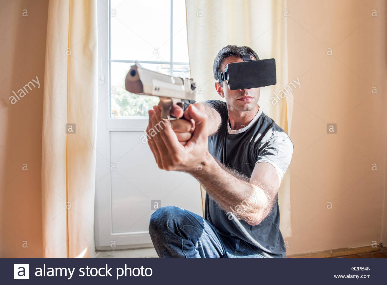 Virtual Reality Gaming - adult man wearing VR headgear goggles, holding a pistol, playing a shooter game at home - Stock Image