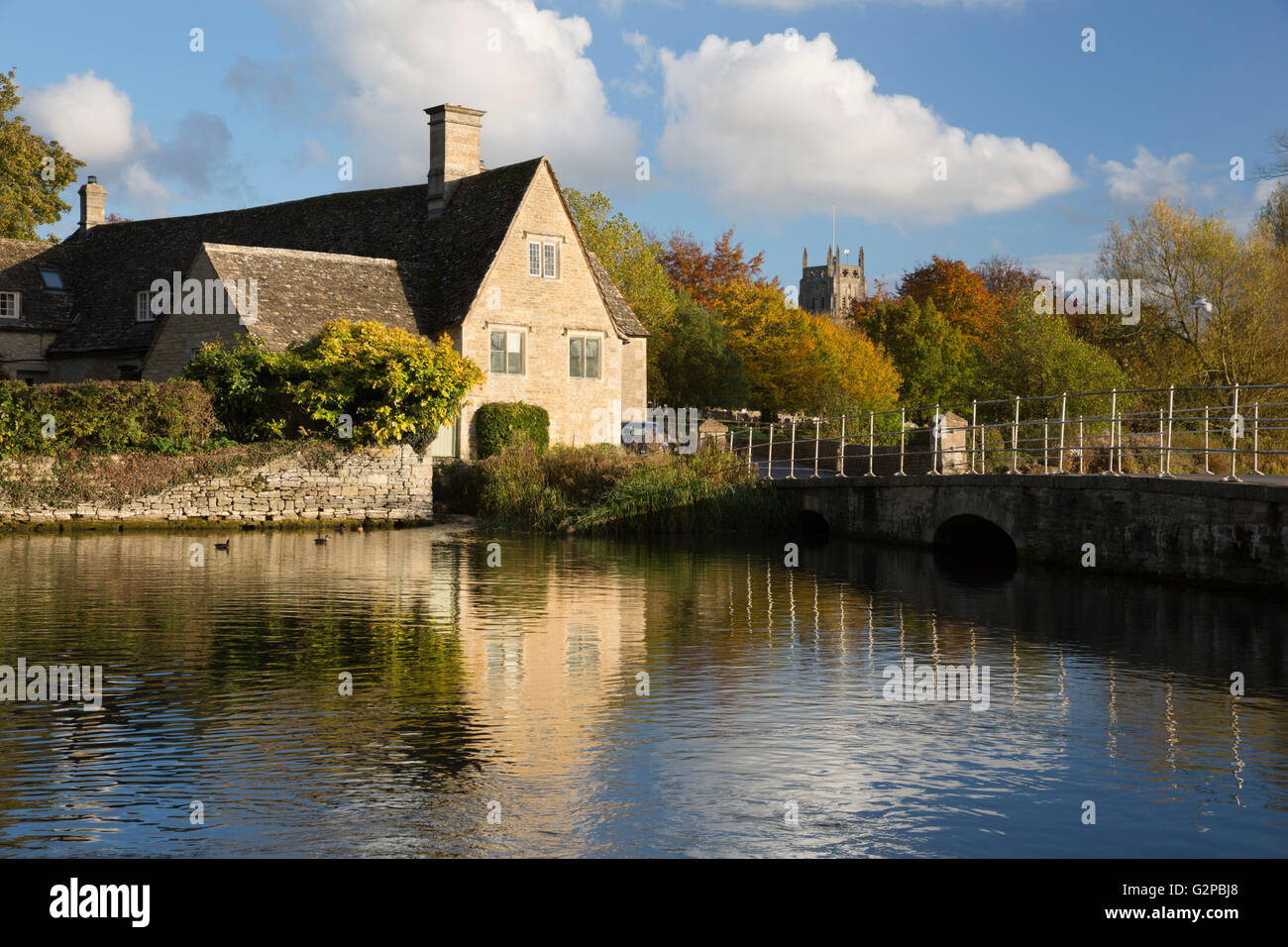Cottage and church on the River Coln in autumn, Fairford, Cotswolds, Gloucestershire, England, United Kingdom, Europe - Stock Image