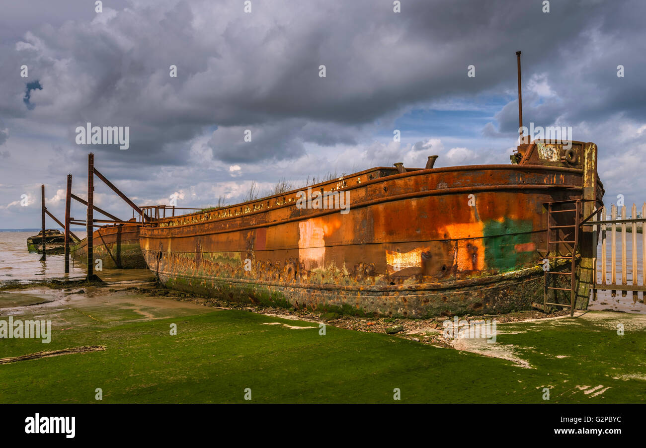 Disused ship yard with derelict, obsolete, and rusting iron ships flanked by mud banks of Humber estuary, Yorkshire, - Stock Image