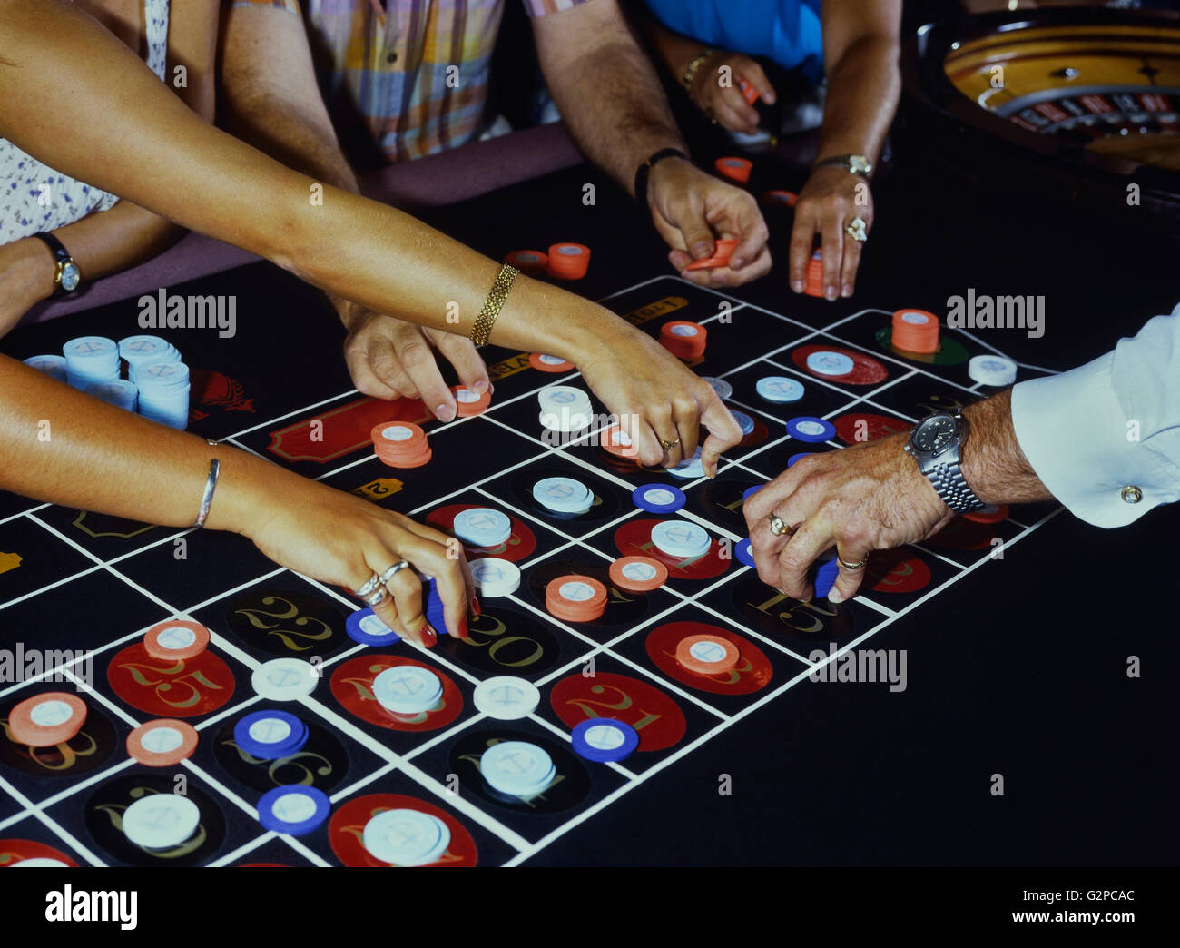 Roulette players and dealer placing chips on the table Stock Photo