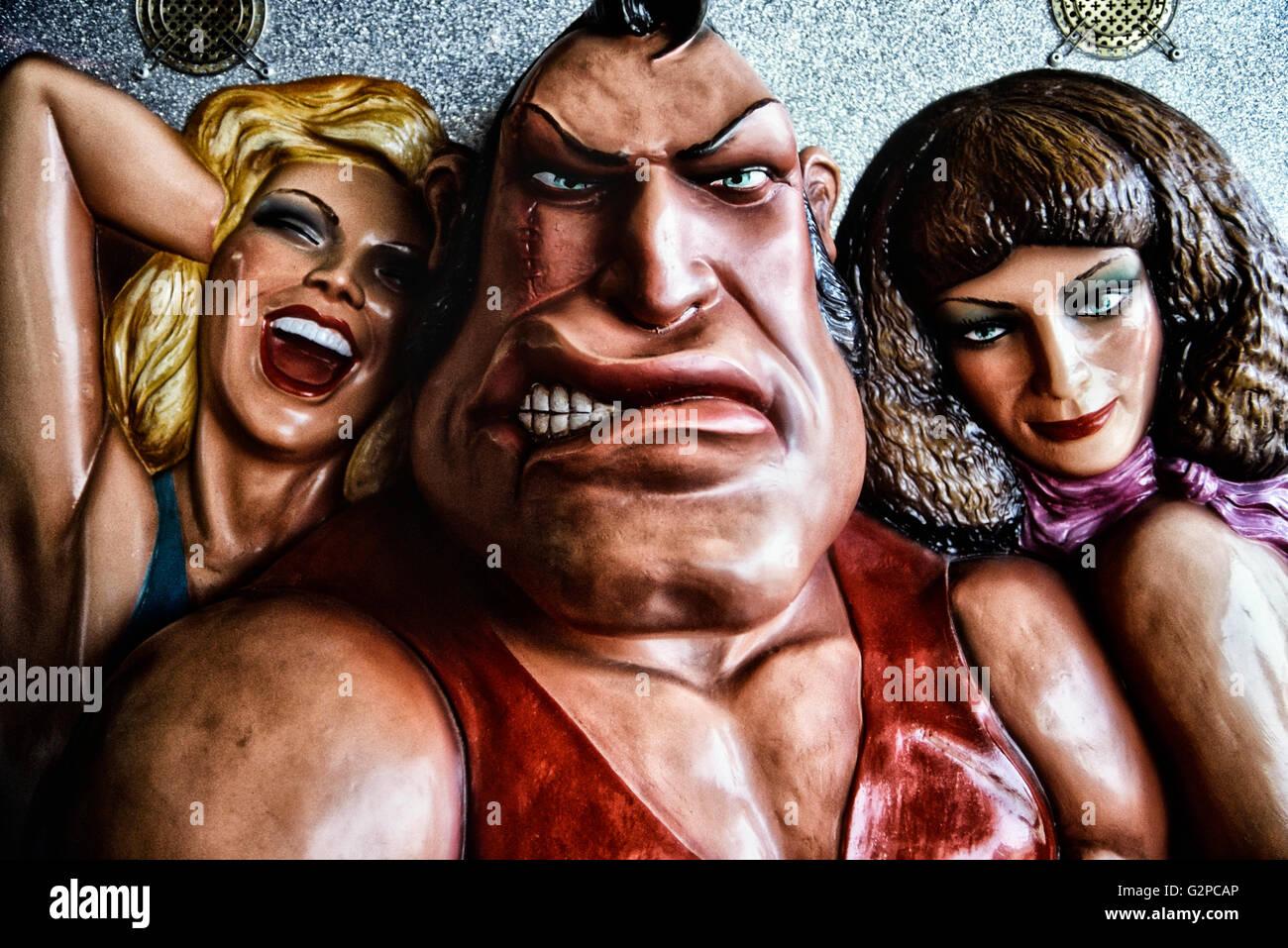 Cartoon figures on an arm wrestling machine - Stock Image
