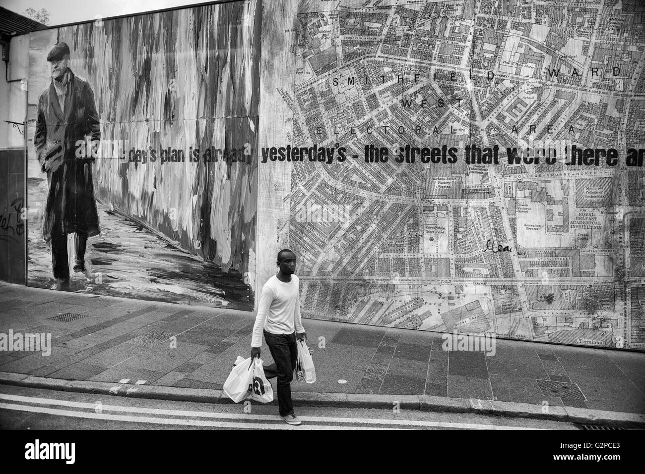 A young African adult carrying his shopping past a giant hoarding on Castle Street. Belfast. Northern Ireland. UK - Stock Image