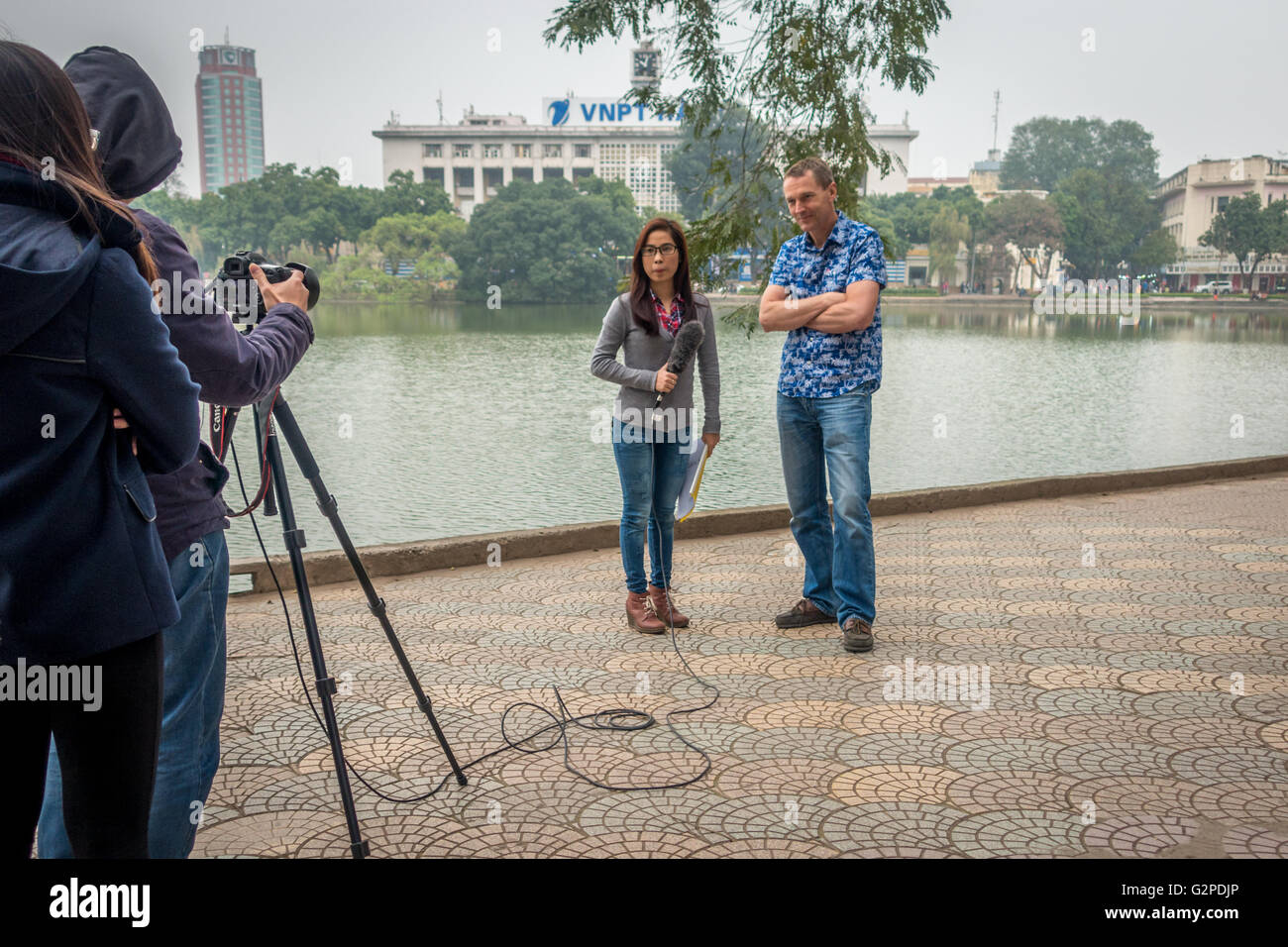 Western male tourist being interviewed by young local Vietnamese woman filming next to the Hoan Kiem Lake, Hanoi, - Stock Image