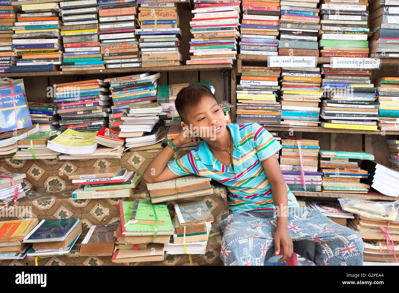 Young secondhand bookseller on the street, Yangon, Yangon State, Myanmar - Stock Image