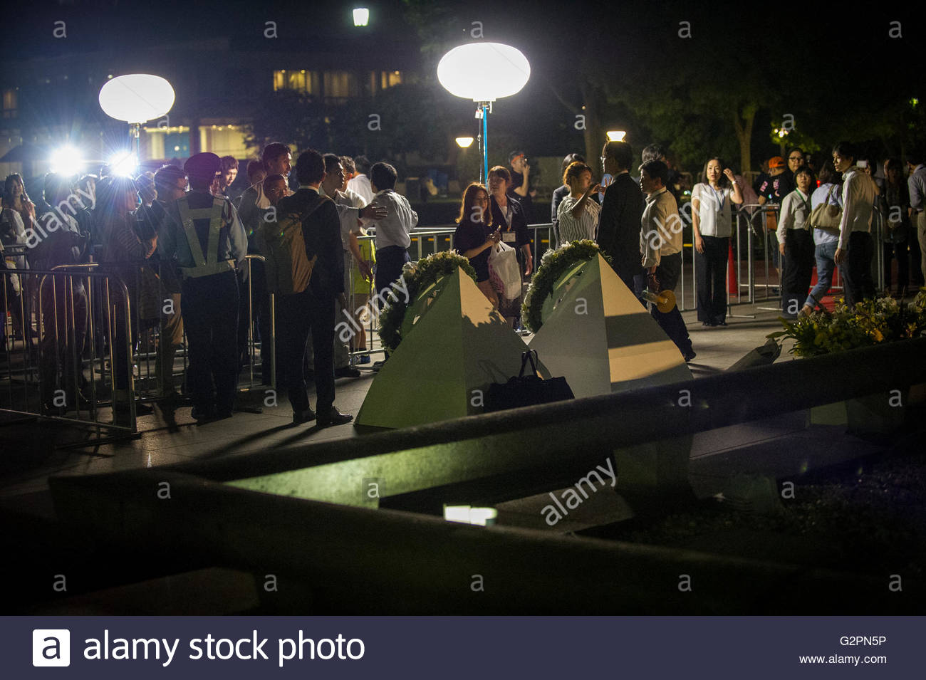 Hiroshima citizens take photographs of the wreath laid by US President Barack Obama at Hiroshima Peace Park during - Stock Image