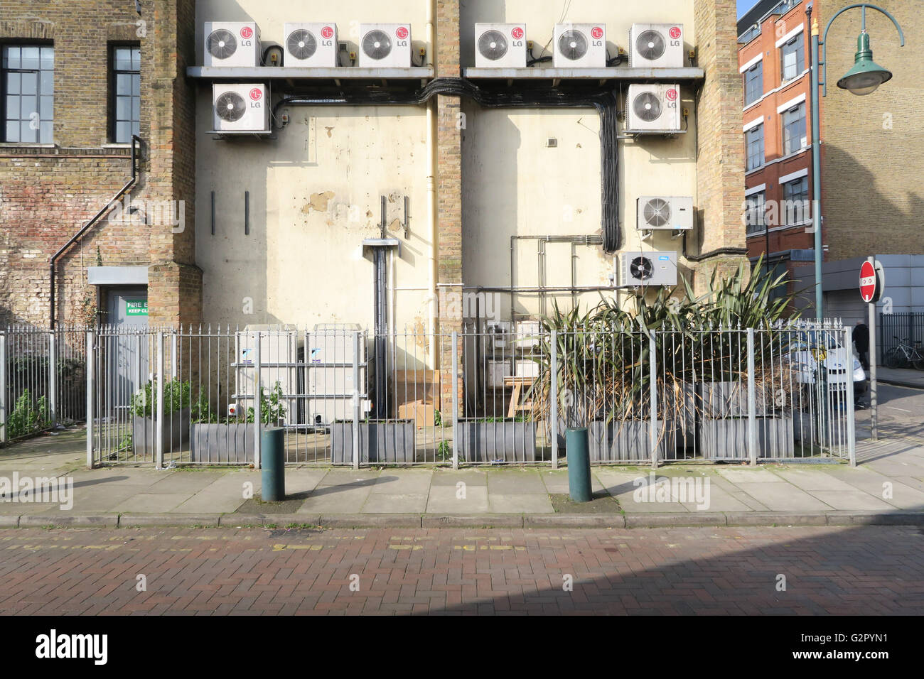 Air conditioning units, metal fence, plants, bollards at the back of a commercial unit - Stock Image