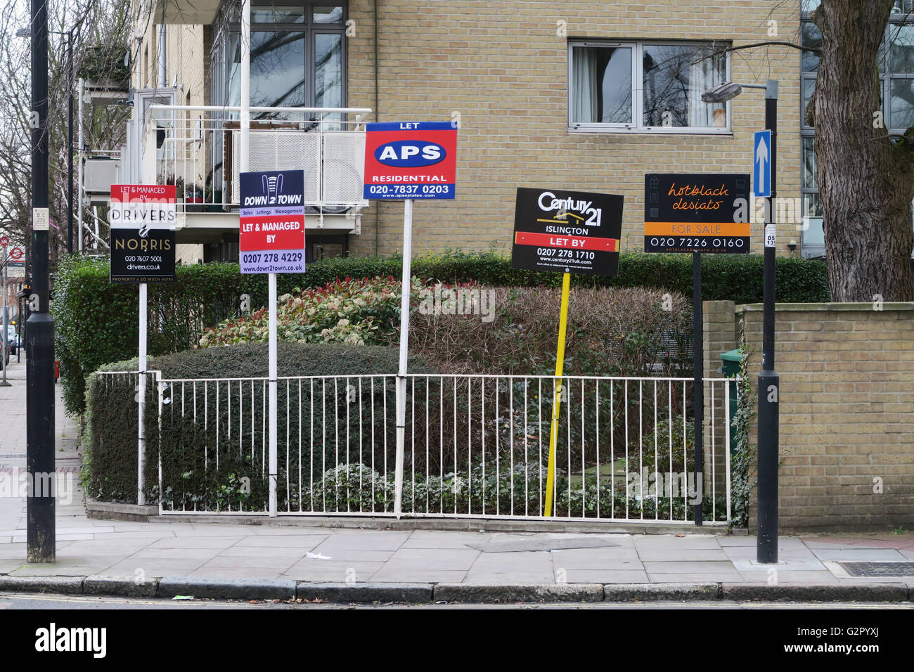 Estate agent for sale / for rent signs attached to a fence - Stock Image